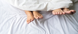couple's foot in the bed